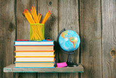 Books and school tools on a wooden shelf. Royalty Free Stock Photos