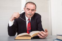 Books. Senior businessman with books in office Stock Image