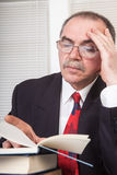 Books. Senior businessman with books in office Stock Photos