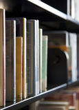 Books on shelf. A close up of a set of books sitting on the shelf of a public library stock image