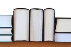 Books on shelf. A row of hard cover books, on wooden shelf, isolated with white background stock images