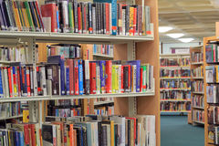 Books on a shelf in library. Stock Photos