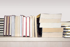 Books on shelf. A pile of different books on a wooden shelf Stock Photos