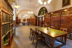 Books on shelves and people reading papers inside historical Royal Danish Library stock photo