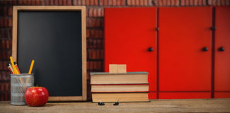 Composite image of books by slate with desk organizer and apple on wooden table Royalty Free Stock Photo