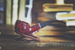 Books and a smoking pipe on a wooden table. Beautiful stylish composition. Toning in the style of vintage. Closeup, soft focus royalty free stock photography