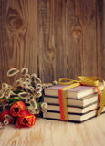 Books and a spring bouquet of tulips and branches of a willow Stock Image