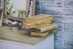 Books stack on the old table in the background of mirrors, candl Stock Photography