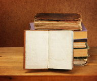 Books stack and opened book. On wooden table. Dark background Stock Photos