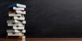 Books stacked on blackboard background. 3d illustration Royalty Free Stock Photography