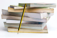 Books stacked and Pencil. Many old books stacked and Pencil leaning beside the book on white background stock photos