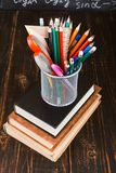 Books and stand for pens on a wooden table. Teacher's day concept and back to school stock photos