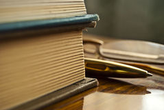 Books. Still life of books pen and glasses lying on a wooden table Royalty Free Stock Image
