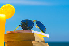Books and sunglasses on a beach Stock Image