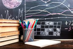 Books on the table against the background of a chalkboard on which are drawn graphs and charts of growth and decline. Business stock image