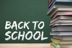 Books on the table against green blackboard with back to school text Royalty Free Stock Images
