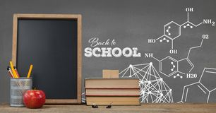 Books on the table against grey blackboard with education and school graphics. Digital composite of Books on the table against grey blackboard with education and Royalty Free Stock Photo