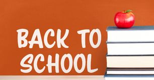 Books on the table against orange blackboard with back to school text. Digital composite of Books on the table against orange blackboard with back to school text Royalty Free Stock Photo