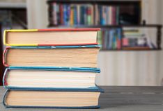 Books on the table on the background of a bookshelf stock images