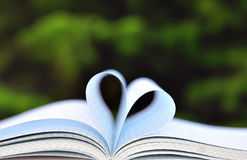 Books on Table in Garden With Top Opened and Pages Forming Heart Royalty Free Stock Photography