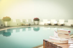 Books on table at swimming pool Stock Photo