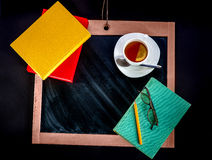 Books with tea on chalkboard with space for text Royalty Free Stock Images