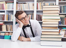 Books to read. Cheerful young man in shirt and bow tie sitting at the table in library and looking at the book stack Stock Images
