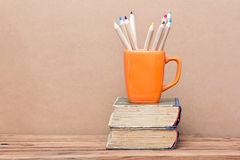 Books tower and orange mug with colored pencils Royalty Free Stock Photos
