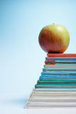 Books tower or stairs with apple. On blue background royalty free stock photos