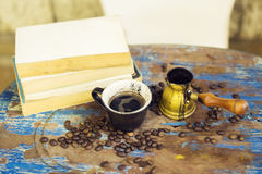Books, turk and coffee on a wooden table Royalty Free Stock Photo