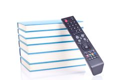 Books or tv?!. Blue books and black remote control - isolated on white Royalty Free Stock Photos