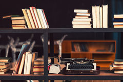 Books and typewriter on wooden shelfs. In the interior royalty free stock image