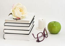 Books on a white background with glasses, apple, rose and candle Royalty Free Stock Images