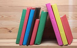Books on wooden shelf close-up. No labels, blank Stock Photos