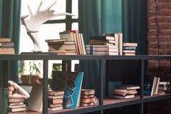 Books on wooden shelfs in the interior. Vintage style royalty free stock photography