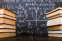 Books on a wooden table, against the background of a chalk board with formulas. Teacher's day concept and back to school royalty free stock photo