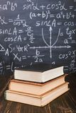 Books on a wooden table, against the background of a chalk board with formulas. Teacher's day concept and back to school. Books on a wooden table, against stock photo