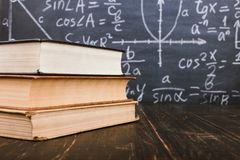 Books on a wooden table, against the background of a chalk board with formulas. Teacher& x27;s day concept and back to school. Books on a wooden table, against stock images