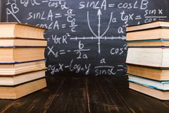 Books on a wooden table, against the background of a chalk board with formulas. Teacher's day concept and back to school. Books on a wooden table, against royalty free stock images