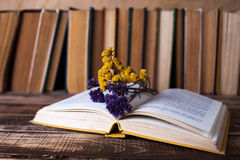 Books. On the wooden table, bead and flowers on the book Stock Image