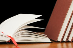 Books on a wooden table on a black background Royalty Free Stock Images