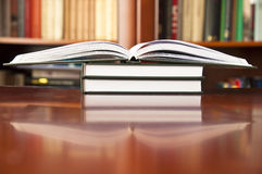 Books on a wooden table. At a library Stock Photos