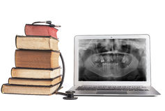 Books and Xray in Laptop. Old Books black stethoscope ans silver laptop isolated on white background royalty free stock images