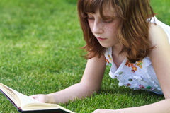 Books.Young beautiful girl reading a book outdoor Stock Photos