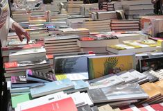 Bookseller and buyer. Books piled on a street bookseller during a street books fair on the books day in the island of Mallorca, Spain royalty free stock images