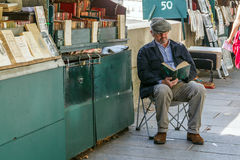 Bookseller on the embankment of the River Seine. Reading a book stock images