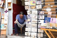 Bookseller Reading Newspaper. Istanbul, Turkey - June 08, 2016: Bookseller reading newspaper sitting in book shop royalty free stock photo
