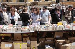 Booksellers on a street books fair. Books piled on a street bookseller during a street books fair on the books day in the island of Mallorca, Spain royalty free stock photography