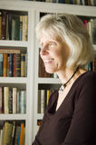 Bookshelf. A pretty mature woman looks out a window with a full bookshelf as backdrop Stock Images