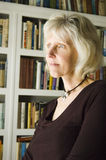 Bookshelf 2. A pretty mature woman looks out a window with a full bookshelf as backdrop Stock Photos